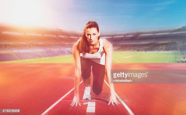 Femme athlète prêt pour la course sur piste de compétition