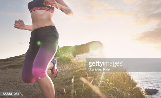 Female athlete running along cliff at sunset
