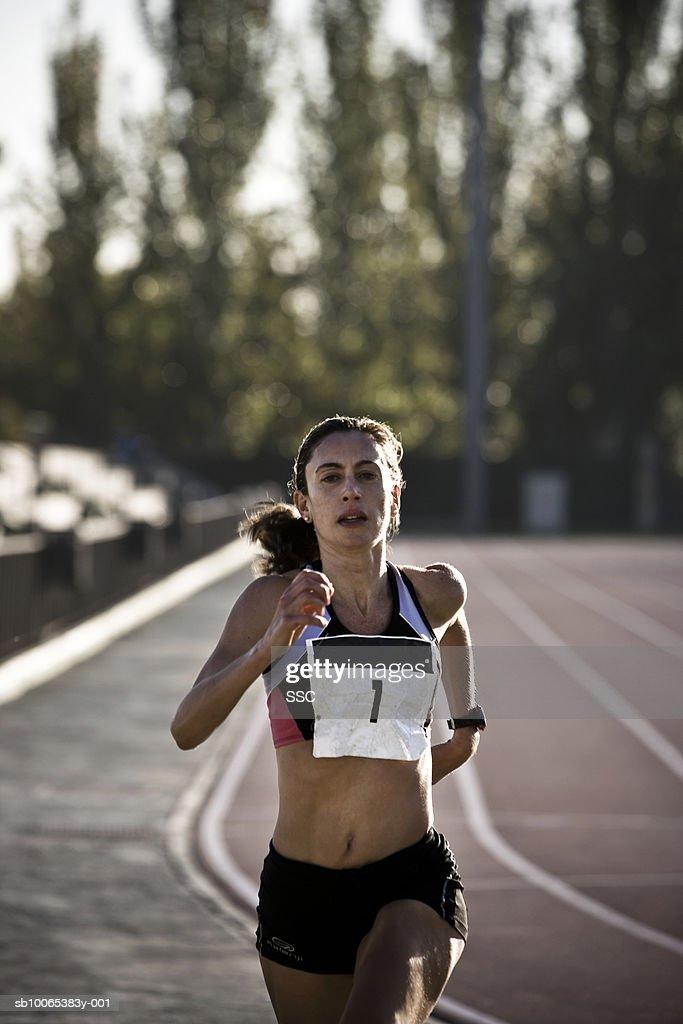 Female athlete running on race track : Stock Photo