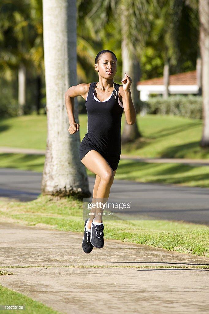 Female Athlete Running on Sidewalk : Stock Photo