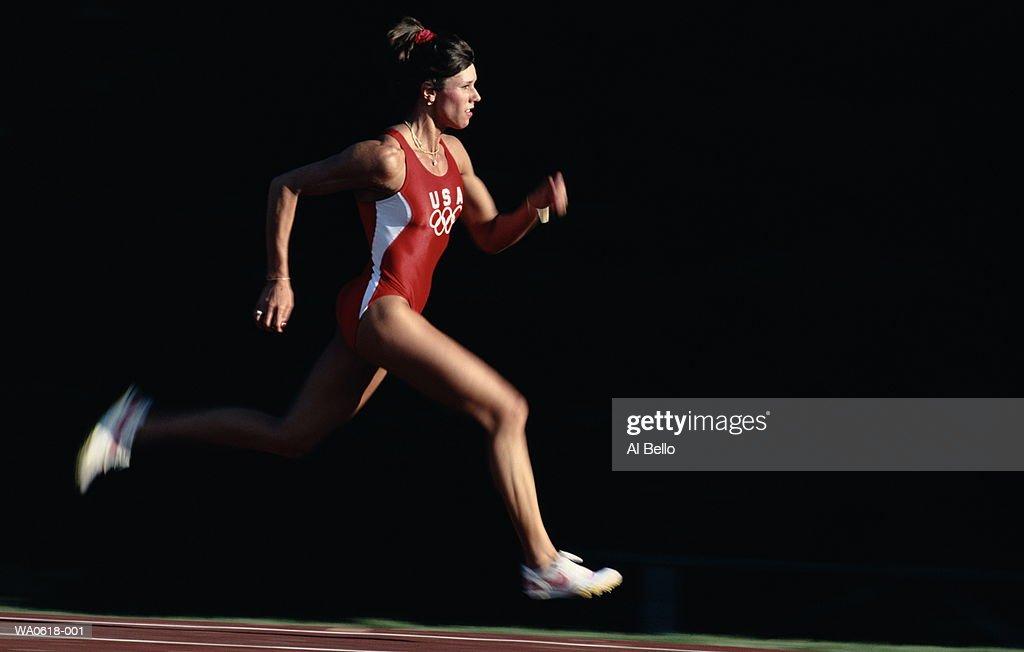 Female athlete running on track, close-up : Stock Photo