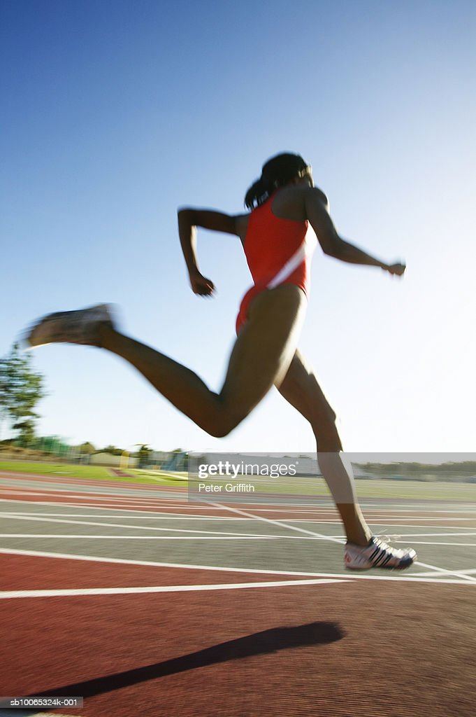 Female athlete running on track, low angle view : Stock Photo