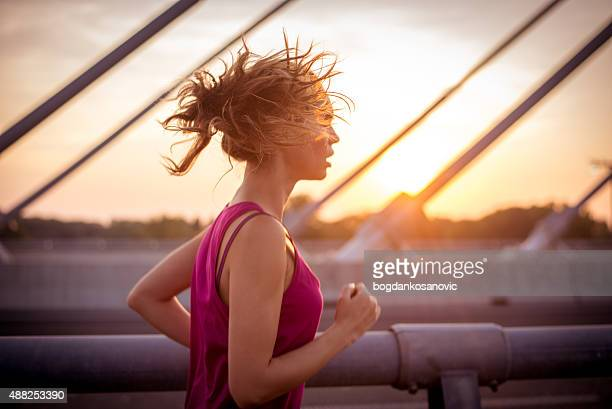 Female athlete running over the bridge in the morning