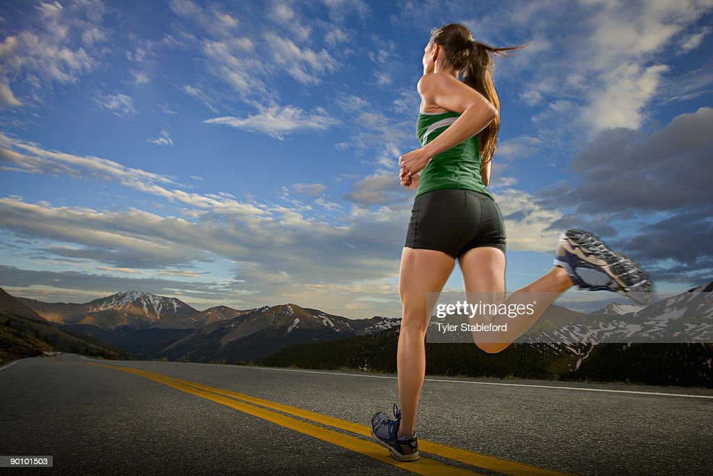 A female athlete runs down a road in the mountains : Stock Photo
