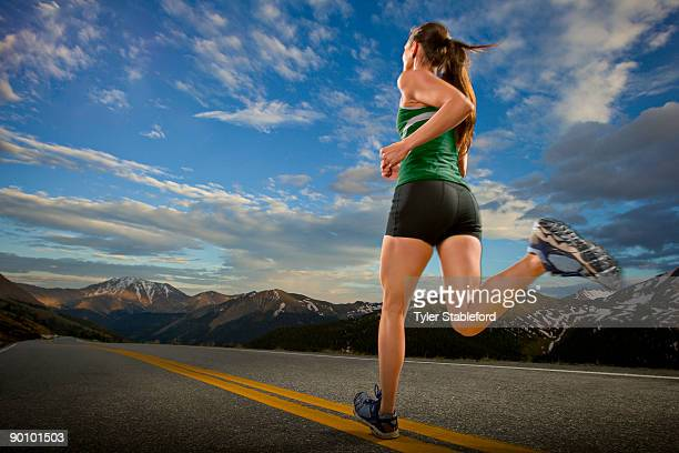 A female athlete runs down a road in the mountains