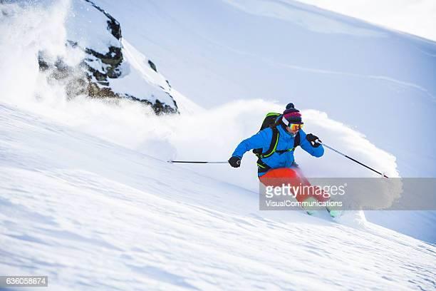 Female athlete skiing in deep powder.