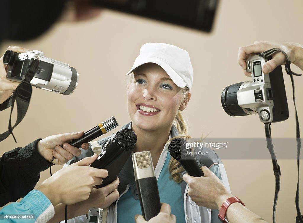 Female athlete smiling at press conference, studio shot