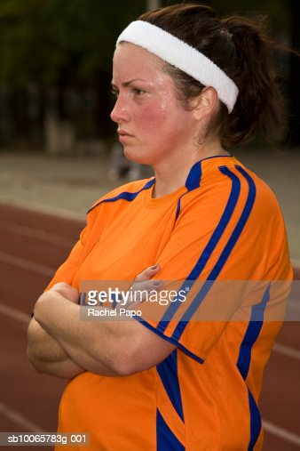 Female athlete standing beside running track : Stock Photo