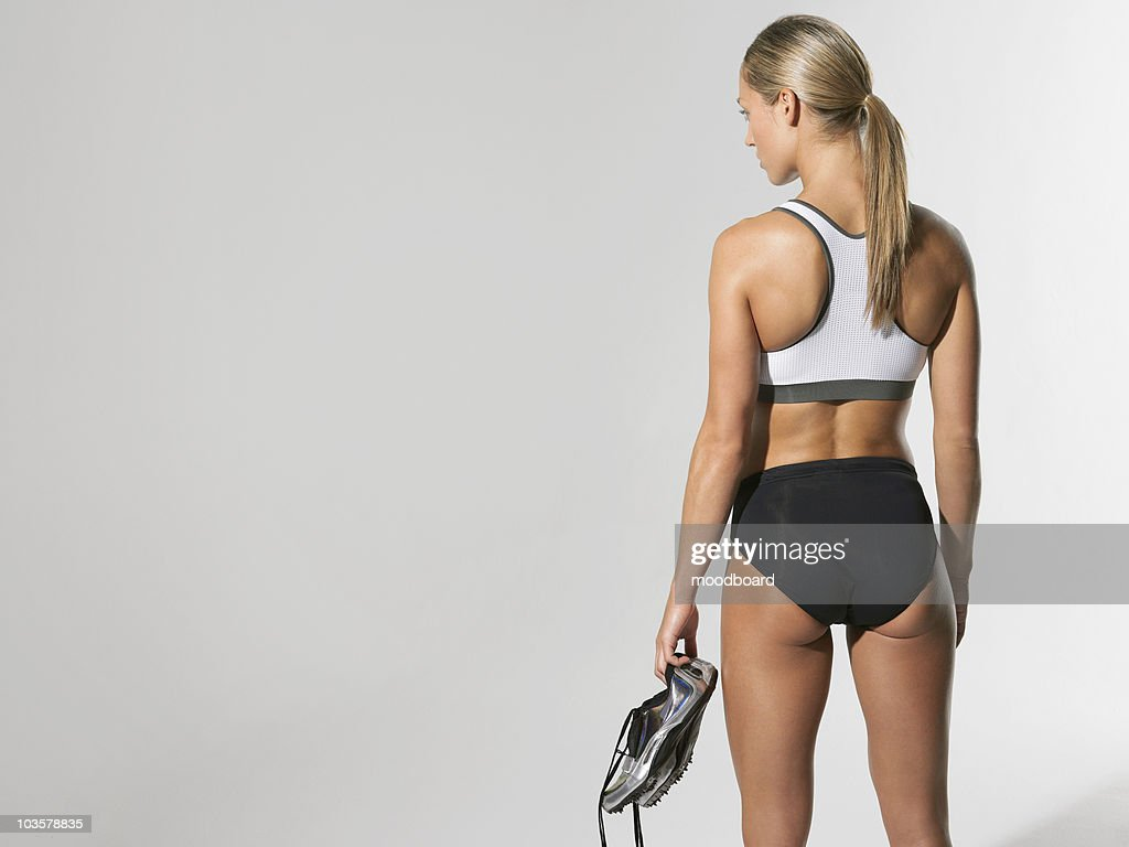 Female athlete standing holding shoes, back view : Stock Photo