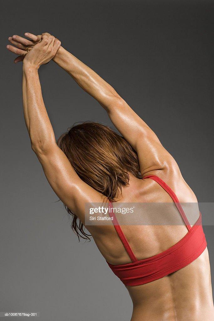 Female athlete stretching, rear view, studio shot : Stock Photo