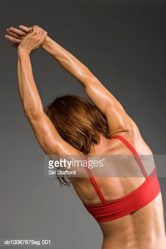 Female athlete stretching, rear view, studio shot : Stock Photo