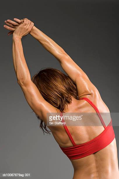 Female athlete stretching, rear view, studio shot