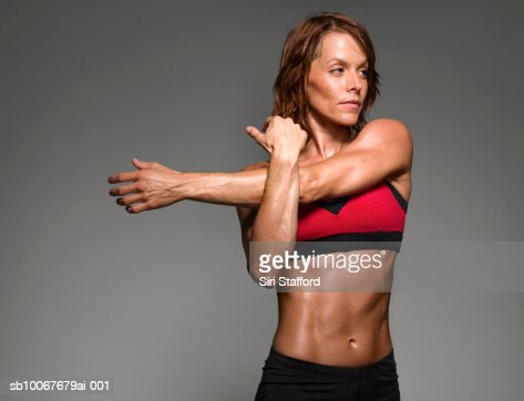 Female athlete stretching, studio shot