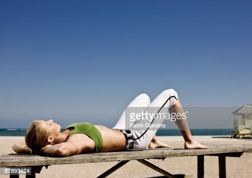 Female athlete stretching, workout on the beach. : Stock Photo
