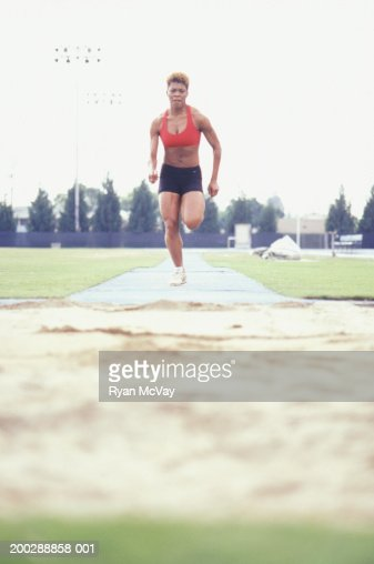 Female athlete taking run-up for long jump, ground view : Stock Photo