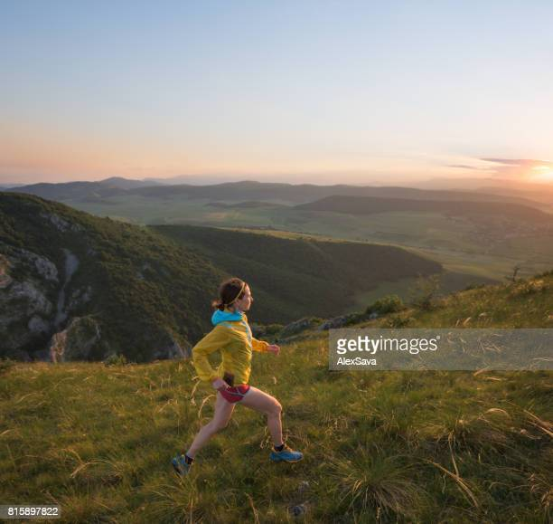 Female athlete trail running on green meadow during sunset