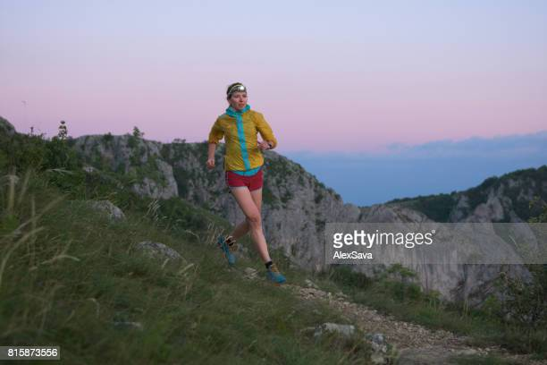 Female athlete wearing headlamp trail running outdoor in the twilight