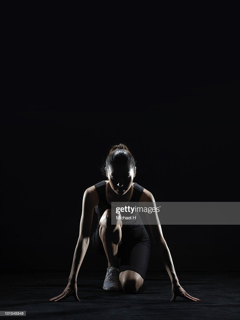 Female athlete who prepares crouch start : Stock Photo