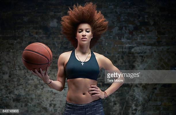 Female athlete with basketball brick background