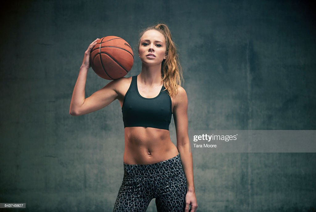 Female athlete with basketball concrete background