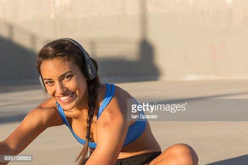 'Female athlete with headphones, stretching, Van Nuys, California, USA'