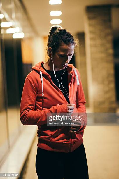 Female athlete zipping her hoodie