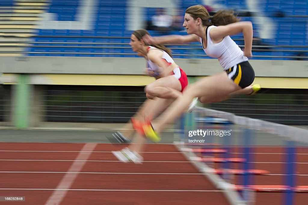 Female athletes at hurdle race 100 m : Stock Photo