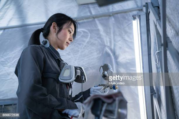 Female autobody technician in an automotive repair shop