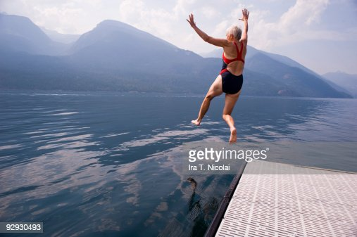 female babyboomer jumping into lake