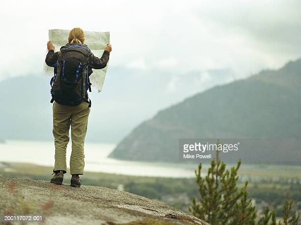 Female backpacker holding map on rock, rear view
