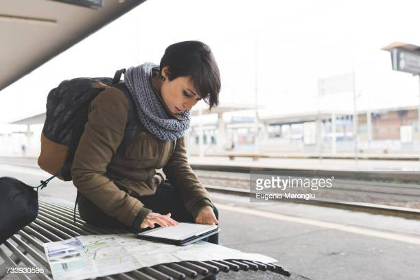 Female backpacker looking at map and digital tablet on railway platform