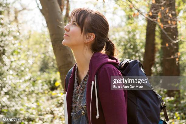 Female backpacker looks up at her surroundings in forest.