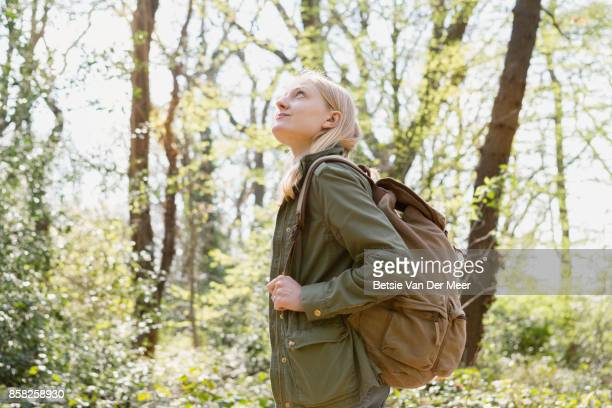 Female backpacker looks up at trees in forest.