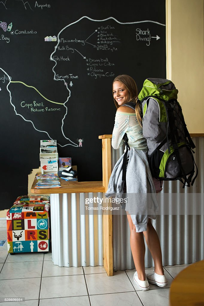 Female backpacker sitting in front of large map : Stock-Foto