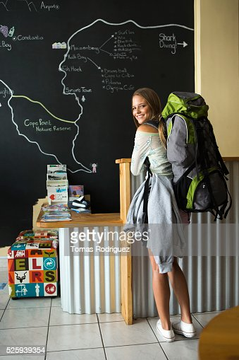 Female backpacker sitting in front of large map : Stock Photo