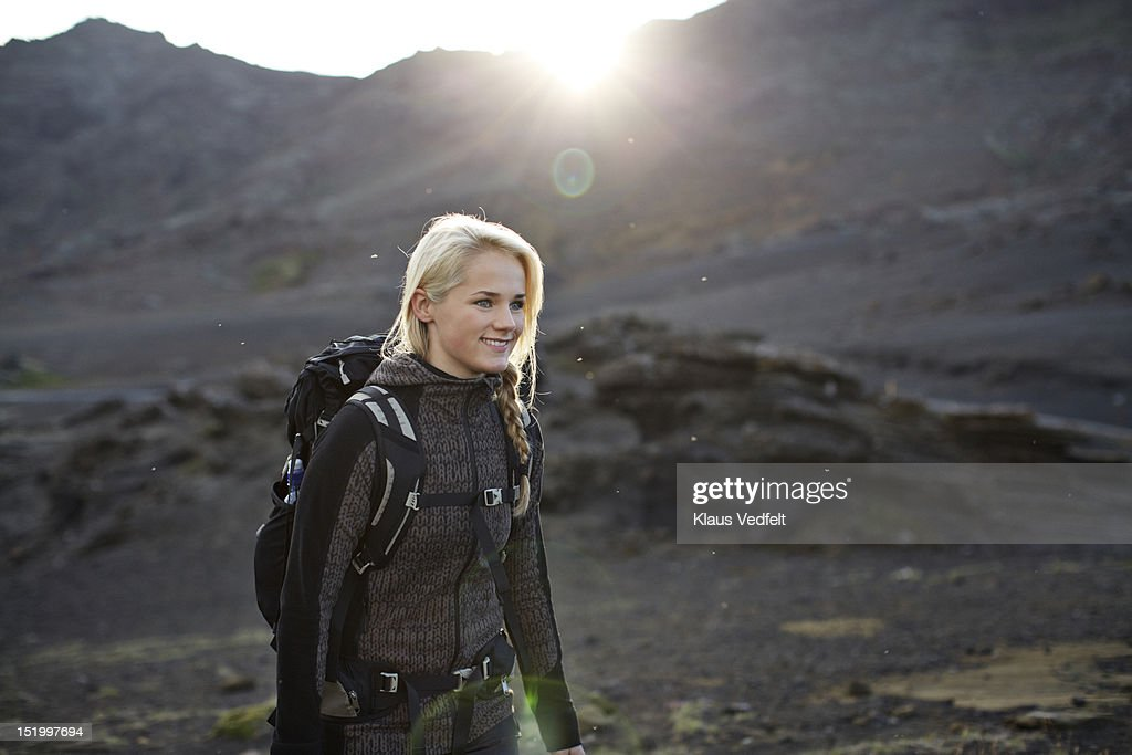 Female backpacker smiling walking in mountain area : Stock Photo