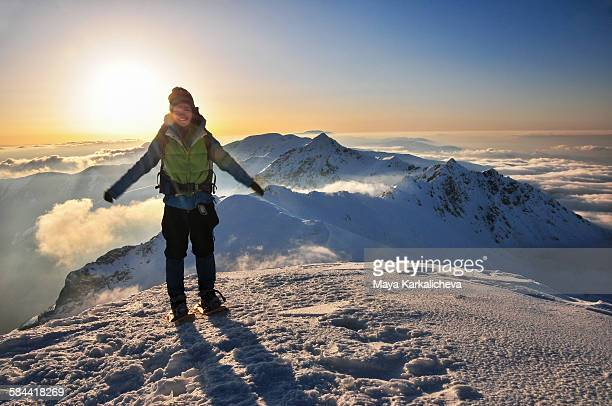 Female backpacker standing on snowy mountain peak