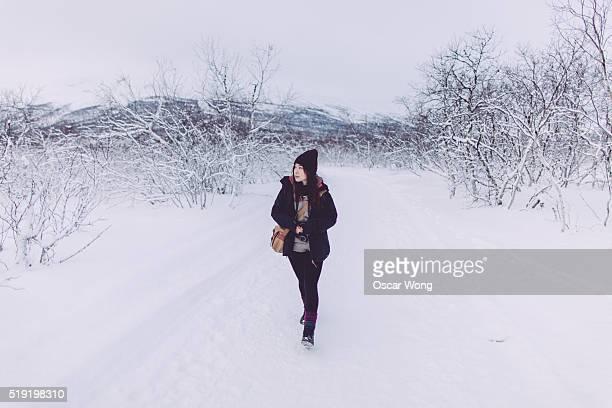 Female backpacker walking in snow