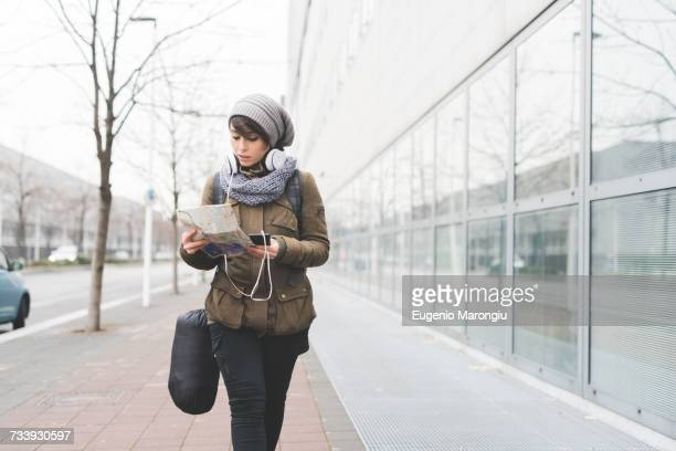 Female backpacker with smartphone looking at map on city sidewalk