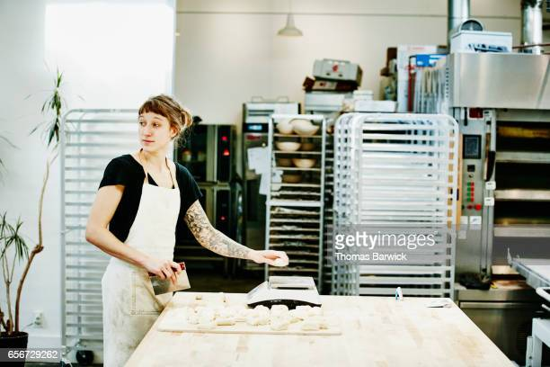 Female baker cutting and weighing dough in bakery