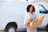 Female Baker Delivering Bread Standing In Front Of Van Smiling To Camera