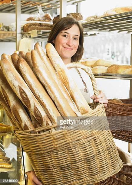 Female baker holding basket of baguettes, smiling, portrait