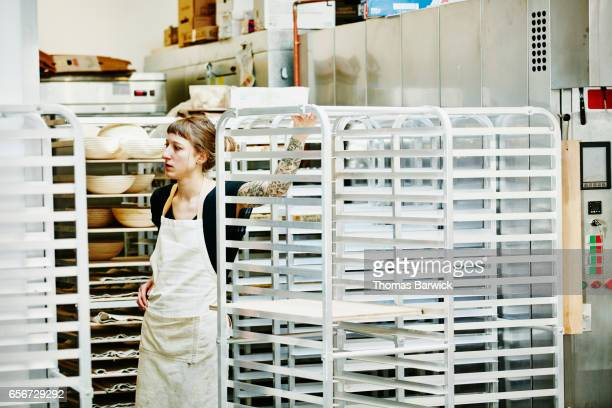 Female baker in discussion with coworker in bakery
