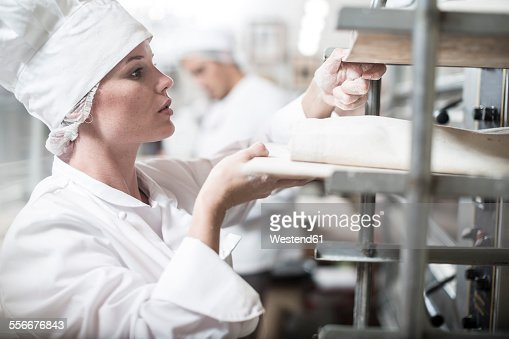 Female baker placing baking trays in oven trolley