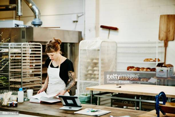Female baker referencing cookbook at counter in bakery