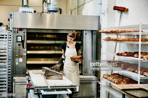 Female baker removing bread from pans fresh from oven