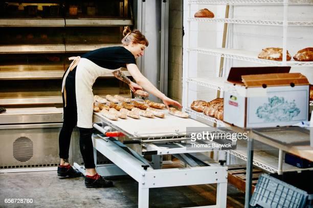 Female baker removing freshly baked baguettes from oven in bakery
