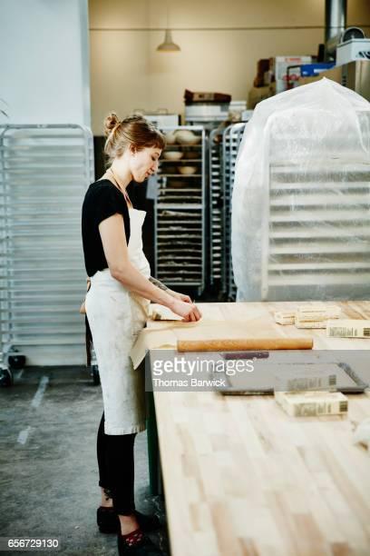 Female baker rolling butter for croissant dough in bakery