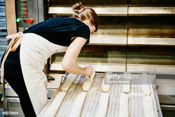 Female baker scoring baguettes before placing in oven for baking
