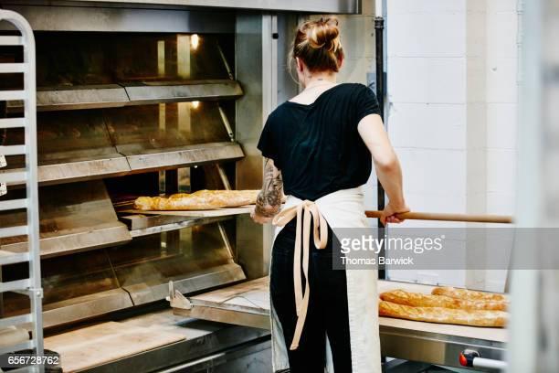 Female baker using peel to remove freshly baked baguettes from oven in bakery